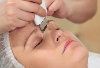 Close-up shot of a woman at beauty spa getting facial treatment with ultrasonic facial cleaning