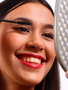 Happy Young Teenager Using A Mirror Making Herself Up Using Mascara
